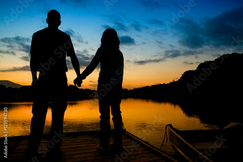 Billede Couple standing by lake at dawn