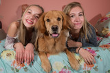 Two young girls with a golden retriever dog at home