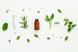 Bottle of essential oil with fresh herbal sage, rosemary, lemon - 123603171