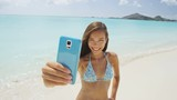 Beach vacation travel woman taking smart phone selfie in bikini having fun sharing on social media. Self portrait photo with smartphone on beach. Happy mixed race Caucasian / Asian Chinese woman.