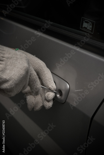 Poster car thief with glove trying to open a vehicle door by screw driver