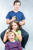 Three children who comb each others head. Efficient head lice treatment, studio portrait shot.