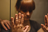 Mirror reflection of sad, depressed woman, with someones hand on her shoulder