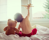 Happy kid playing with wooden toy airplane and Teddy bear in bed