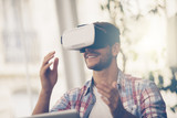 Entrepreneurs testing virtual reality technology with colleague