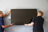 Two Men Fitting Flat Screen Television To Wall