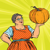 Cheerful grandmother with pumpkin for Thanksgiving