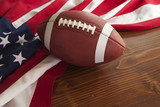 Football with American flag on dark pine wood background
