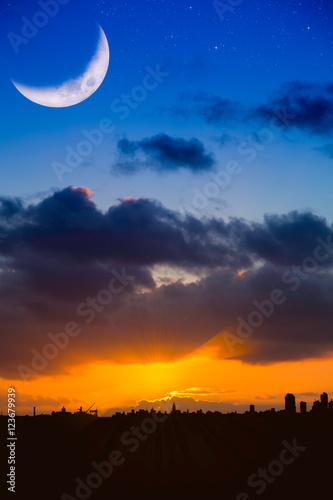 Fotografiet City Skyline  at Sunrise or Sunset with Moon and Stars