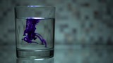 Blue colorant is dissolved in glass of water