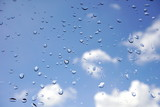 water drops on glass of window with blur background of blue sky and clouds