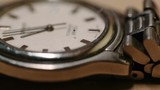 Old father watches time lapse video. Steel Wrist Watch closeup