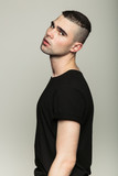 Studio shoot of young man wearing black t-shirt turned away and looking at camera. Side view.