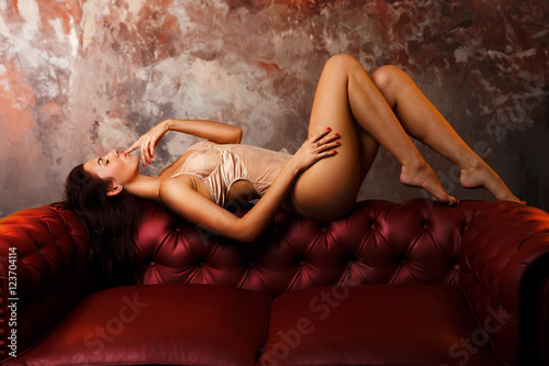 sexy girl on the red sofa. playful mood - 123704114