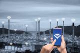 Hand holding smartphone control wireless communication network