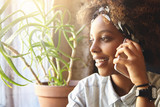 People, technology and communication concept. Portrait of good-looking stylish African woman having nice phone conversation, talking to her best friend, listening attentively and with interest