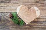 Carved wooden heart and larch branch with cone on a background o