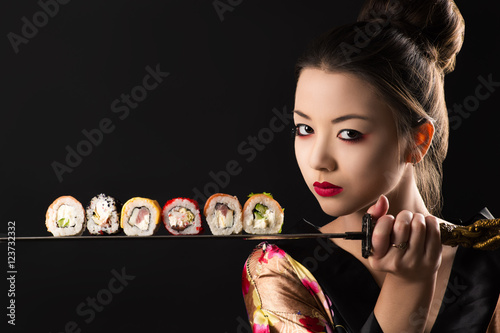 Foto op Plexiglas Sushi bar beautiful girl samurai with sword and rolls