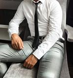 Hombre joven con traje, sentado en sillón.