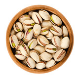 Roasted pistachio seeds with shell in wooden bowl on white background. Pistacia vera fruits and kernels. Isolated macro food photo close up from above. - 123750740