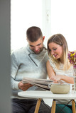 Happy young couple is spending morning together reading news. Young mixed-raced man is sitting at the dining table with his beautiful blonde girlfriend, having a breakfast and reading the newspaper.