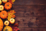 Fototapety Thanksgiving background: Apples, pumpkins and fallen leaves on wooden background. Copy space for text. Halloween, Thanksgiving day or seasonal background. Design mock up.