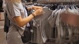 Shopping Woman Choosing Clothes in Clothing Store