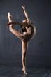 Refined woman dance in studio at dark wall