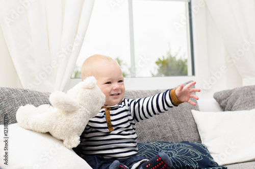 Poster Kleiner Junge lacht mit seinem Teddy