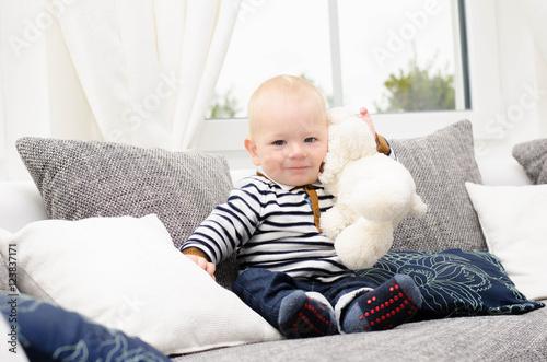 Kleiner Junge kuschelt mit seinem Teddy Poster