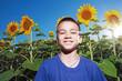 Постер, плакат: счастливый мальчик в поле с подсолнухами
