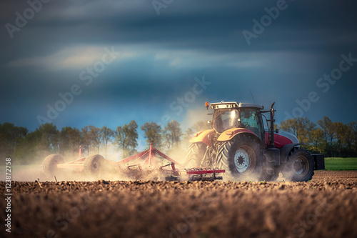 Poster Farmer in tractor preparing land with seedbed cultivator