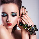 Beautiful woman face with green make-up and glass jewelry, creat