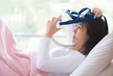 Woman lay in bed wearing CPAP mask ,sleep apnea therapy. Happy and healthy woman,sleep apnea,wearing CPAP mask