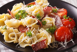 Italian food: tortellini with prosciutto and parmesan close-up on a plate. Horizontal