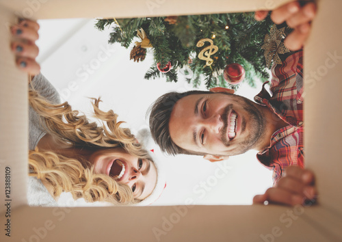 Young couple opening a Christmas present, view from inside of the box