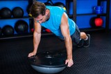 Young man with BOSU ball in gym