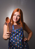 The red-haired hostess with a wooden spoon in her hand. Cooking in the kitchen.