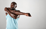 African man with muscular build stretching arms