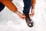 close up of man tying boot shoelaces in winter