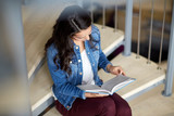 high school student girl reading book on stairs