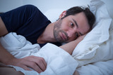 Depressed man lying in his bed and feeling bad - 123922146