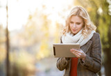Beautiful blonde woman with tablet in colorful autumn park