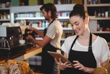 Smiling waitress standing at counter using digital tablet