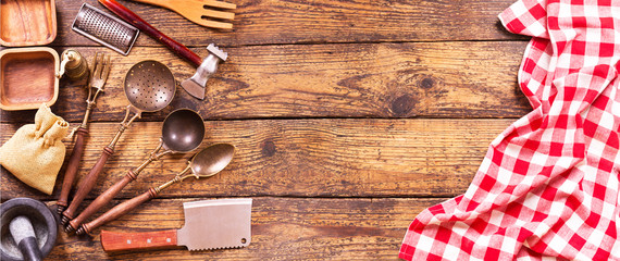 Various kitchen utensils on wooden table © Nitr