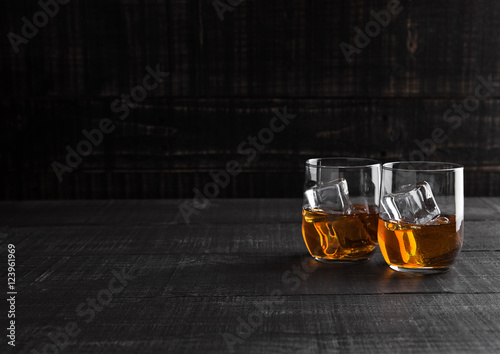 Glasses of whiskey with ice on wooden background