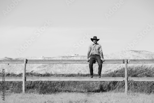 cowboy sitting on a fence Poster