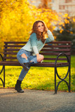 Happy young fashion woman with long curly hairs sitting on bench