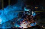 Worker with protective mask welding automotive part in factory - 123984134