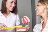Zahnärztin vermittelt Patientin die korrekte Mundhygiene